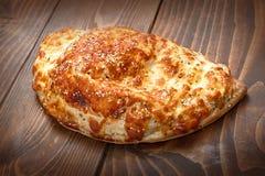 Italienische Piroguepizza auf Holztisch mit dem Schmelzen des gebackenen Käses lizenzfreie stockfotos