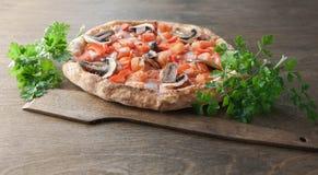 Italienische Pizza auf einem braunen hölzernen Hintergrund lizenzfreie stockfotos