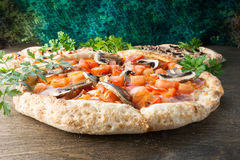 Italienische Pizza auf einem braunen hölzernen Hintergrund Lizenzfreies Stockfoto