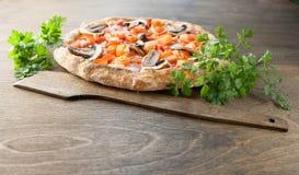 Italienische Pizza auf einem braunen hölzernen Hintergrund Stockfotografie