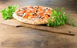Italienische Pizza auf einem braunen hölzernen Hintergrund lizenzfreie stockbilder