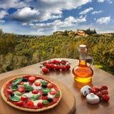 Italienische Pizza im Chianti gegen Olivenbäume und Landhaus in Toskana, Italien lizenzfreie stockbilder