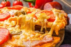 Italienische Pizza mit Tomaten und Pilzen auf einem hölzernen Brett lizenzfreies stockbild