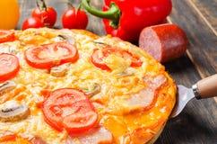 Italienische Pizza mit Tomaten und Pilzen auf einem hölzernen Brett stockfotografie