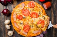 Italienische Pizza mit Tomaten und Pilzen auf einem hölzernen Brett lizenzfreies stockfoto