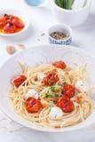 Italienische Spaghettiteigwaren mit gebackenen Kirschtomaten, Mozzarella und Frühlingszwiebeln Lizenzfreie Stockbilder