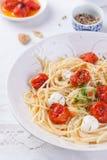 Italienische Spaghettiteigwaren mit gebackenen Kirschtomaten, Mozzarella und Frühlingszwiebeln Lizenzfreie Stockfotos
