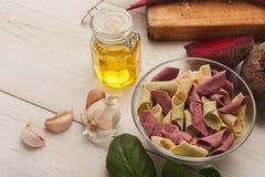Italienische Teigwaren in den Schüsseln und Lorbeer treiben auf weißem Holz Blätter lizenzfreie stockbilder