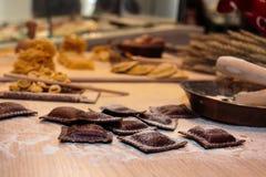 Italienische Teigwaren der schwarzen Ravioli auf hölzernem Brett mit Mehl Lizenzfreies Stockbild