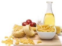 Italienische Teigwaren, Makkaronispulen mit Kirschtomaten und Olivenöl in einer Glasflasche lizenzfreie stockfotografie