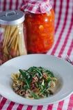 Italienische Teigwaren mit Raketensalat und -schinken auf dem Tisch Stockfotografie