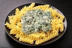 Italienische Teigwaren mit Spinatssoße auf Schwarzblech Lizenzfreies Stockfoto