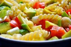 Italienische Teigwaren mit Tomaten, Avocado und Zwiebel Stockbild