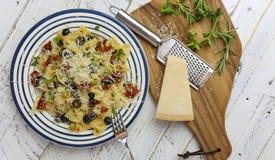 Italienische Teigwaren-Platte mit den grünen und schwarzen Oliven, Parmesankäse-Schach Lizenzfreie Stockfotografie