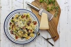 Italienische Teigwaren-Platte mit den grünen und schwarzen Oliven, Parmesankäse-Schach Stockfotos
