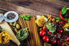 Italienische und Mittelmeerlebensmittelinhaltsstoffe auf altem hölzernem Hintergrund Lizenzfreie Stockbilder