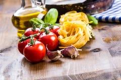 Italienische und Mittelmeerlebensmittelinhaltsstoffe auf hölzernem Hintergrund Kirschtomatenteigwaren, Basilikumblätter und Karaf Stockbild
