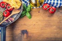 Italienische und Mittelmeerlebensmittelinhaltsstoffe auf hölzernem Hintergrund Kirschtomatenteigwaren, Basilikumblätter und Karaf Lizenzfreies Stockfoto