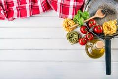 Italienische und Mittelmeerlebensmittelinhaltsstoffe auf hölzernem Hintergrund Kirschtomatenteigwaren, Basilikumblätter und Karaf Lizenzfreies Stockbild