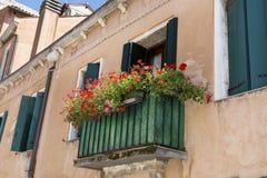 Italienischer Balkon der schönen Weinlese mit rotem Topf blüht Stockbilder