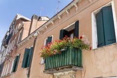 Italienischer Balkon der schönen Weinlese mit rotem Topf blüht Lizenzfreie Stockfotos
