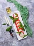 Italienischer caprese Salat mit Mozzarella, Tomaten und Basilikum Lizenzfreie Stockfotografie