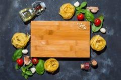Italienischer Fettuccine nistet mit Tomaten, Olivenöl und Basilikum in Form eines Rahmens mit einem hölzernen Brett mit einem Kop lizenzfreie stockbilder