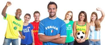 Italienischer Fußballfan mit den gekreuzten Armen und anderen Fans stockbilder