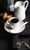 Italienischer Kaffeesatz für Frühstück Schale heißen Espresso, Rahmtopf mit Milch-, cantucci- und mokatopf auf dunklem rustikalem Stockfotos