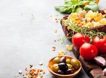 Italienischer Lebensmittelhintergrund mit Rebtomaten, Basilikum, Spaghettis, Oliven Bestandteile auf Steintabelle Kopienraum Stockfotografie