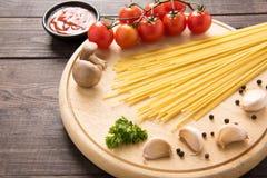 Italienischer Lebensmittelhintergrund, mit Tomate, Knoblauch, Pfeffer, Spaghettis Stockfotografie