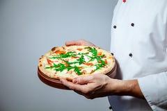 Italienischer Mannchefkoch, der eine fertige Pizza auf einem grauen Hintergrund hält stockfotos