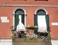 Italienisches Gebäude der schönen roten Weinlese mit Balkon mit Topf blüht Lizenzfreie Stockfotos