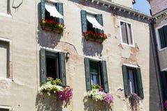 Italienisches Gebäude der schönen Weinlese mit Fenstern mit rotem Topf blüht Lizenzfreie Stockfotografie