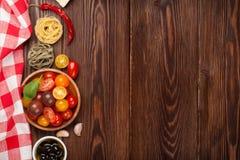 Italienisches Lebensmittel, das Bestandteile kocht Teigwaren, Gemüse, Gewürze Stockfotografie