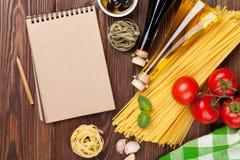 Italienisches Lebensmittel, das Bestandteile kocht Teigwaren, Tomaten, Basilikum Stockfotos