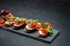 Italienisches Lebensmittel mit Oliven und Prosciutto bruschettas auf Steinbrett Stockbilder