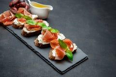 Italienisches Lebensmittel mit Oliven und Prosciutto bruschettas auf Steinbrett Lizenzfreies Stockfoto