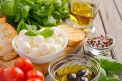 """Italienisches Lebensmittelinhaltsstoffe †""""Mozzarella, Tomaten, Basilikum und Olivenöl auf rustikalem hölzernem Hintergrund Stockfoto"""