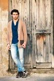 Italienisches Modell des gutaussehenden Mannes nahe einer alten Holztür Lizenzfreies Stockfoto