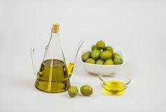 Italienisches Olivenöl mit grünen Oliven auf weißem Hintergrund Lizenzfreies Stockfoto