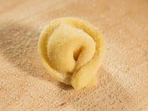 Italienisches selbst gemachtes tortellino gesetzt auf den Holztisch, besprüht mit Mehl Stockbild
