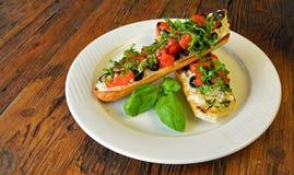 Italienisches Tomate bruschetta mit Oliven auf hölzernem Stockfotos