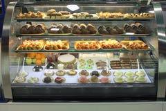 Italiensk bakelse shoppar med den olika babaen, donuts, gelé, glass, kakor med frukter och bär Arkivbild