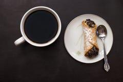 Italiensk cannoli med chokladchiper på den vita platta- och kaffekoppen på svart bakgrund Royaltyfri Fotografi