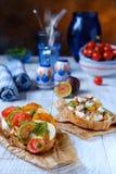 Italiensk crostini med osttomaten på vitt trä fotografering för bildbyråer