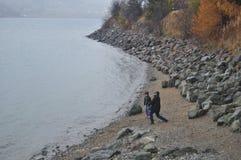 Italiensk fader och son som spelar på stenstranden av Resias sjön Arkivbild
