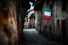 Italiensk flagga som hänger på forntida byggnad arkivbild