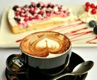 Italiensk frukost med cappuccino- och fruktkakan Arkivfoto