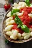 Italiensk gnocchi med tomaten och basilika Arkivfoto